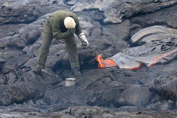 Scientist in protective gear sampling lava using a rock hammer and a bucket of water.