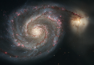 A pair of galaxies, one spiral and the other irregularly shaped. The edges of the spiral galaxy appear to be reaching toward the second galaxy.