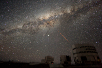 Image of the night sky above Paranal on 21 July 2007, taken by ESO astronomer Yuri Beletsky. A wide band of stars and dust clouds, spanning more than 100 degrees on the sky, is seen. This is the Milky Way, the Galaxy we belong to. At the centre of the image, two bright objects are visible. The brightest is the planet Jupiter, while the other is the star Antares. Three of the four 8.2-m telescopes forming ESO's VLT are seen, with a laser beaming out from Yepun, Unit Telescope number 4. The laser points directly at the Galactic Centre. Also visible are three of the 1.8-m Auxiliary Telescopes used for interferometry. They show small light beams which are diodes located on the domes. The exposure time is 5 minutes and because the tracking was made on the stars, the telescopes are slightly blurred.