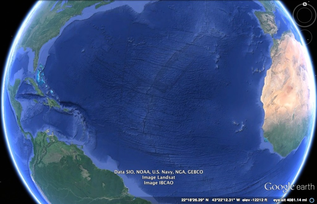 Satellite view of the Pacific Ocean. Parts of North America, South America, Africa, and Europe are visible. The ocean's differing depths are visible.