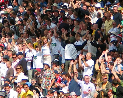 A photo of a large group of people all sitting on stadium benches