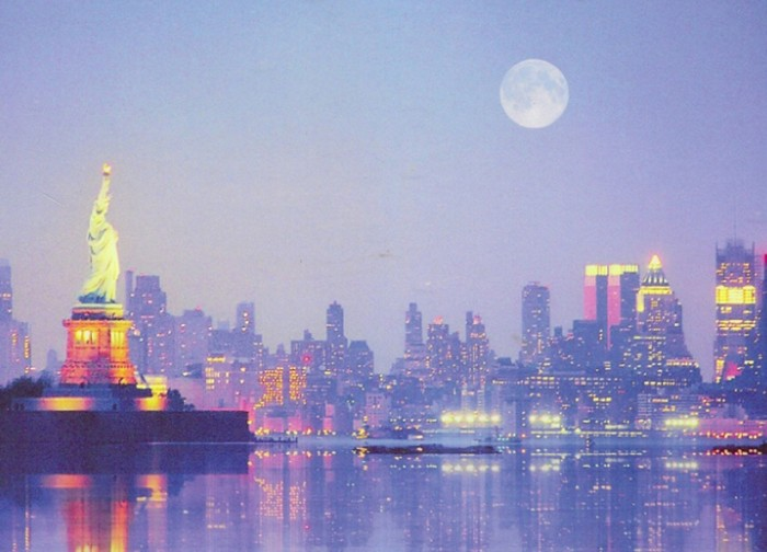 A panorama of New York Harbor at dusk with a full moon in the sky