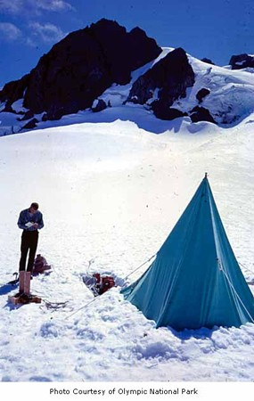 A man is shown taking notes outside a tent in the mountains.