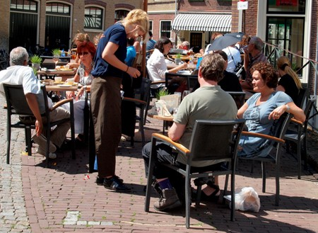 Waitress serves customers in an outdoor café.