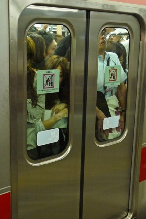 A crowd of people behind closed subway car doors is shown.