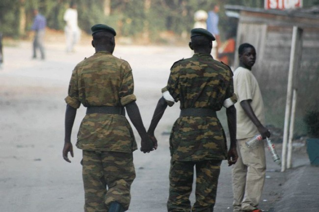 Two Male Sol Rs In Uniform Are Shown From Behind Walking And Holding Hands