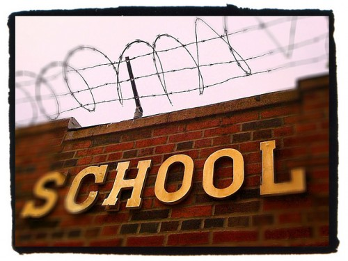 """A brick wall is shown with the word """"school"""" on it and barbed wire on top."""