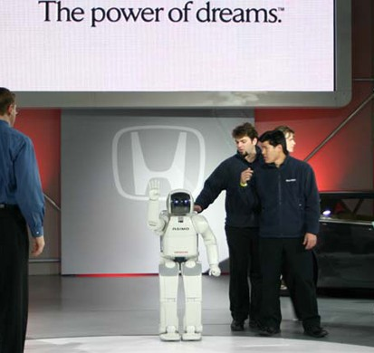 A photo of a small robot getting patted on the back by two men.