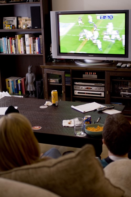 A boy and girl are shown from behind watching a football game on television. A coffee table sits between them and the television, and a bookshelf is beside the TV.
