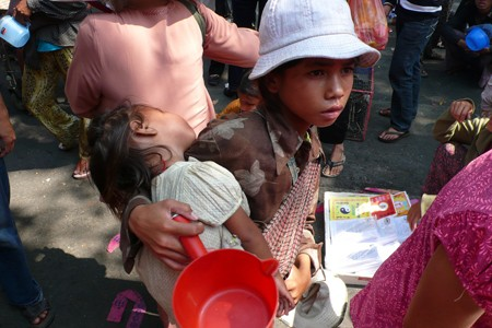 A young, impoverished boy is shown holding a baby girl.
