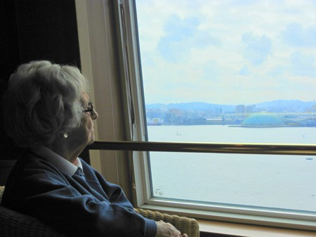 An older woman with white hair and glasses is shown looking out a window, across a body of water.