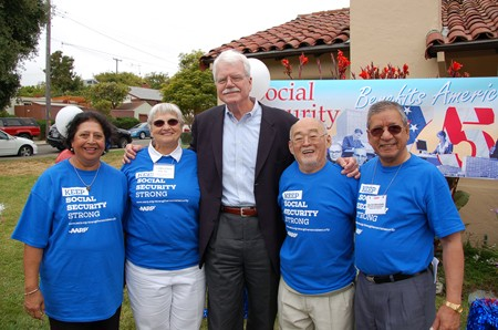 """A tall man with white hair and moustache and glasses in casual business attire is shown flanked by two elderly women on his right and two elderly men on his left. The elderly people are all wearing blue T-shirts reading """"Keep Social Security Strong: A A R P."""" A banner in the background can also be seen, reading """"Social Security Benefits America."""""""