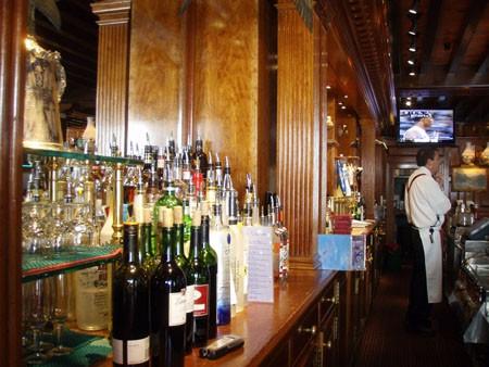 A bartender standing behind a bar.