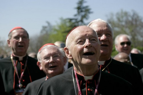 About a half-dozen older men wearing Roman Catholic priestly garb are shown from the shoulders up.