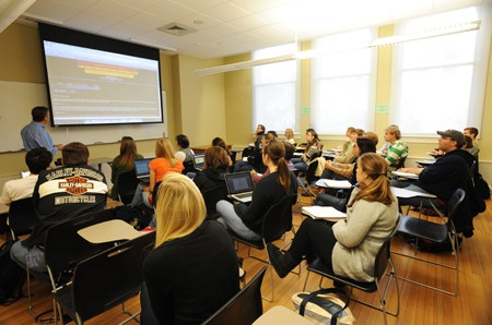 Teacher and high school students in a classroom looking at the projection screen in the front of the classroom.