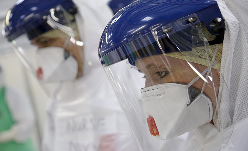 This photo depicts medical workers with a face mask and gloves training for safety so they can enter infection zones.