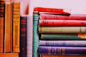 Photo of brightly colored vintage books. Those on the left are standing vertically, while those on the right are lying stacked horizontally