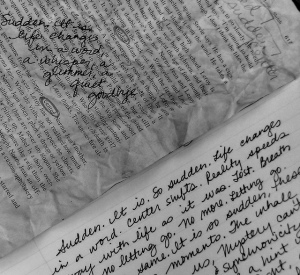 Photo of a crumpled piece of printed text with handwriting on top of it, lying over handwriting on a notebook page