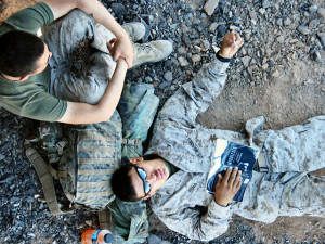 Photo looking down on a US Marine in fatigues lying on the ground with an open copy of the book Middlesex open on his chest. Another Marine sits near his head, with his knees to his chin.