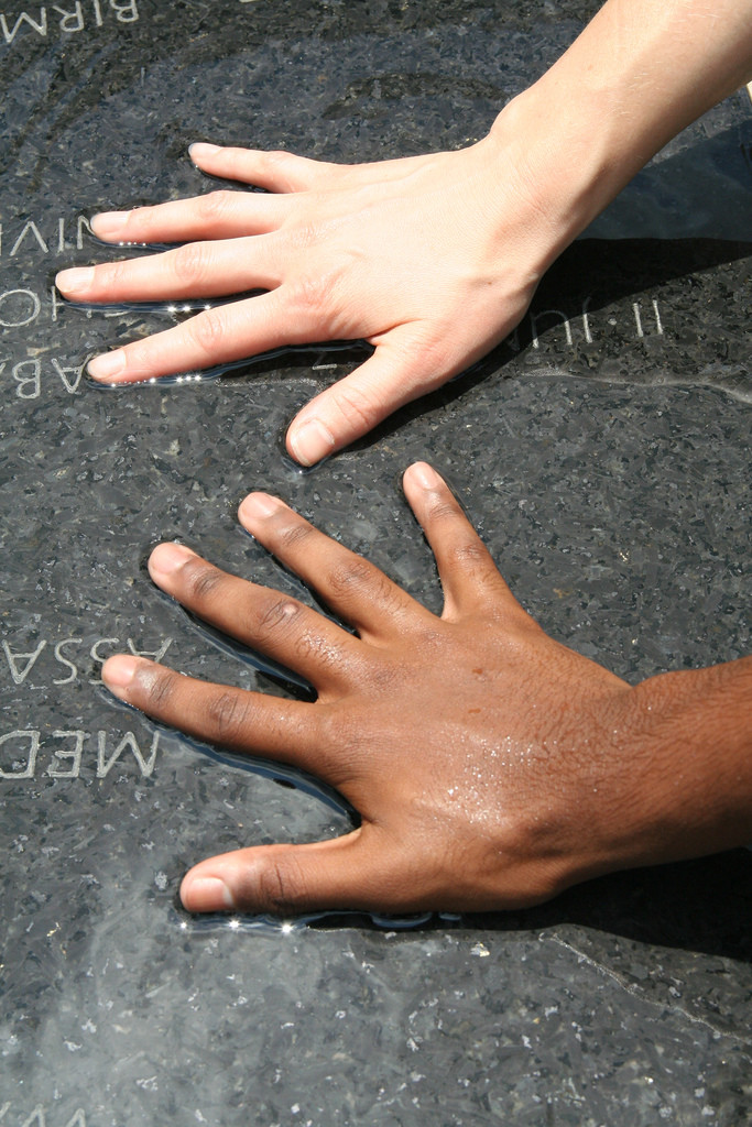 Photo of two hands, one white, one brown, side by side, fingers outstretched.