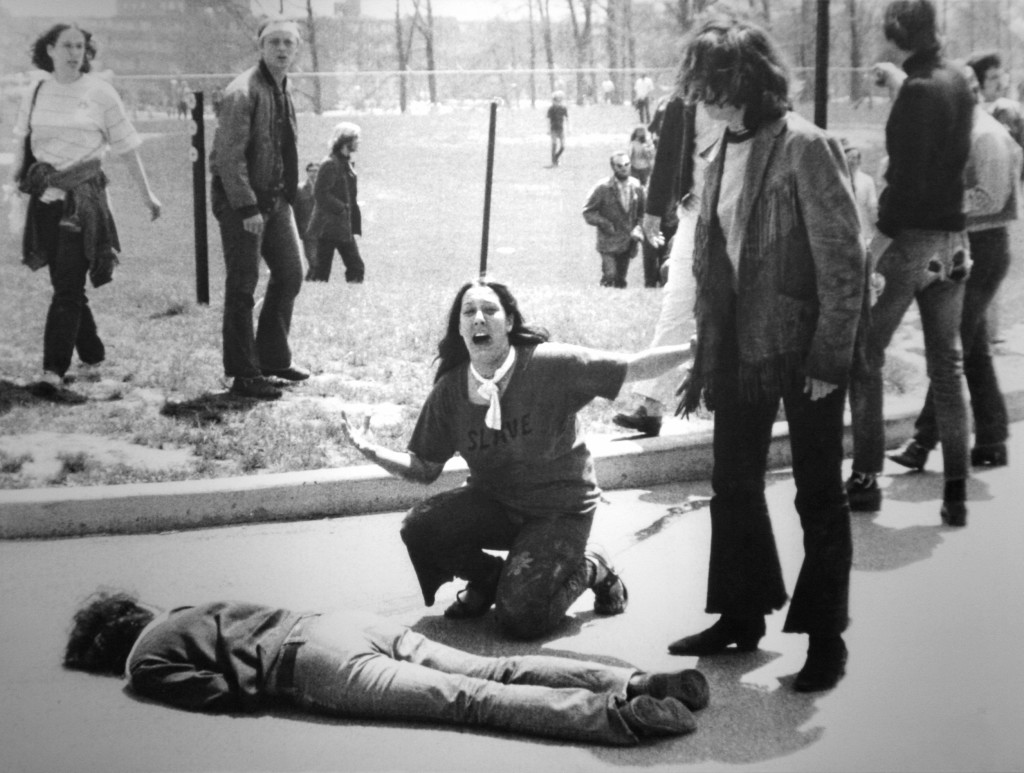 Black-and-white photo showing an anguished woman, her mouth open and arms outstretched, kneeling beside the body of a slain boy.