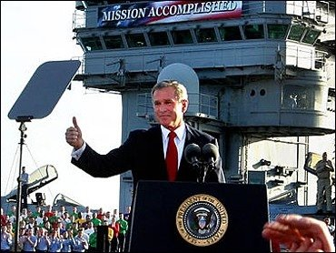 "Photo of President George W. Bush giving the thumbs-up sign with a large sign in the background that reads, ""Mission Accomplished."""