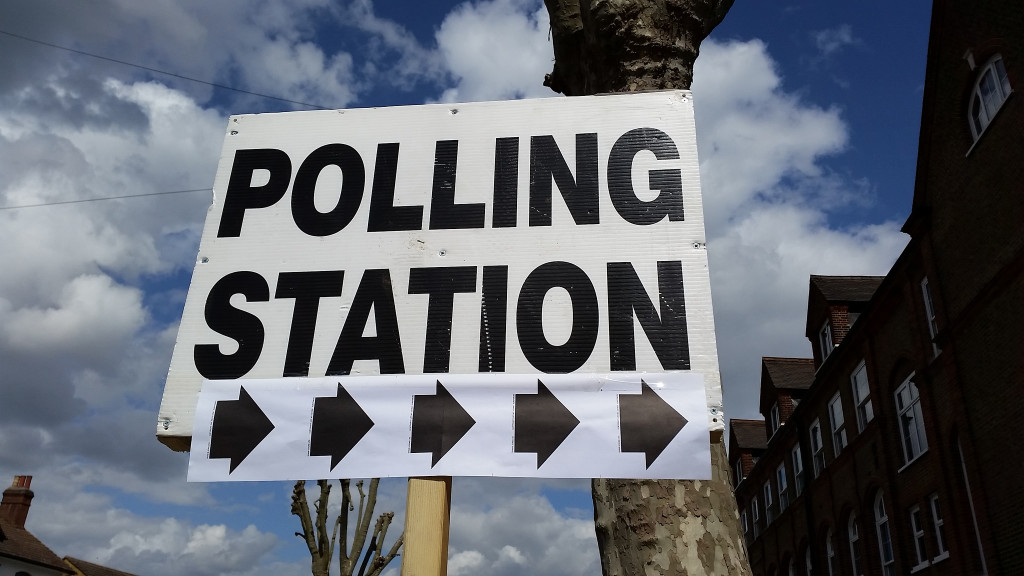 "Photo of a sign that reads, ""Polling Station."" A view of blue sky and clouds in the background"