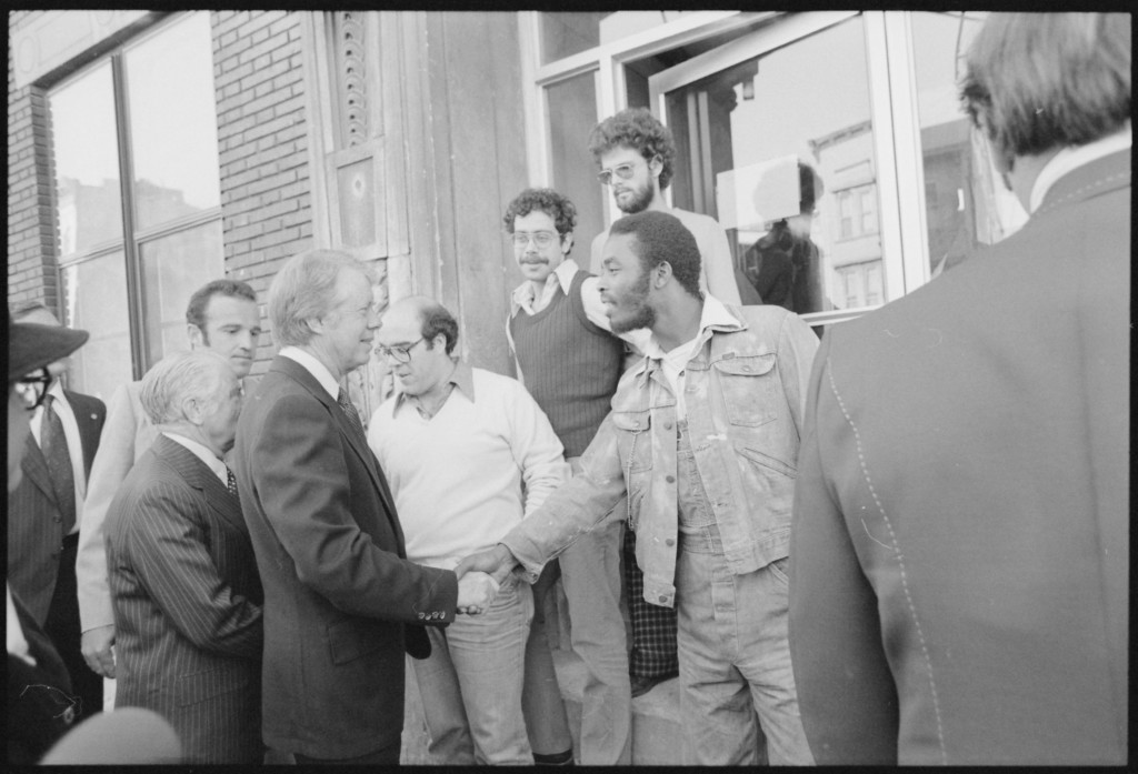 Black-and-white photo showing President Carter shaking hands with several residents of the Bronx, NYC.