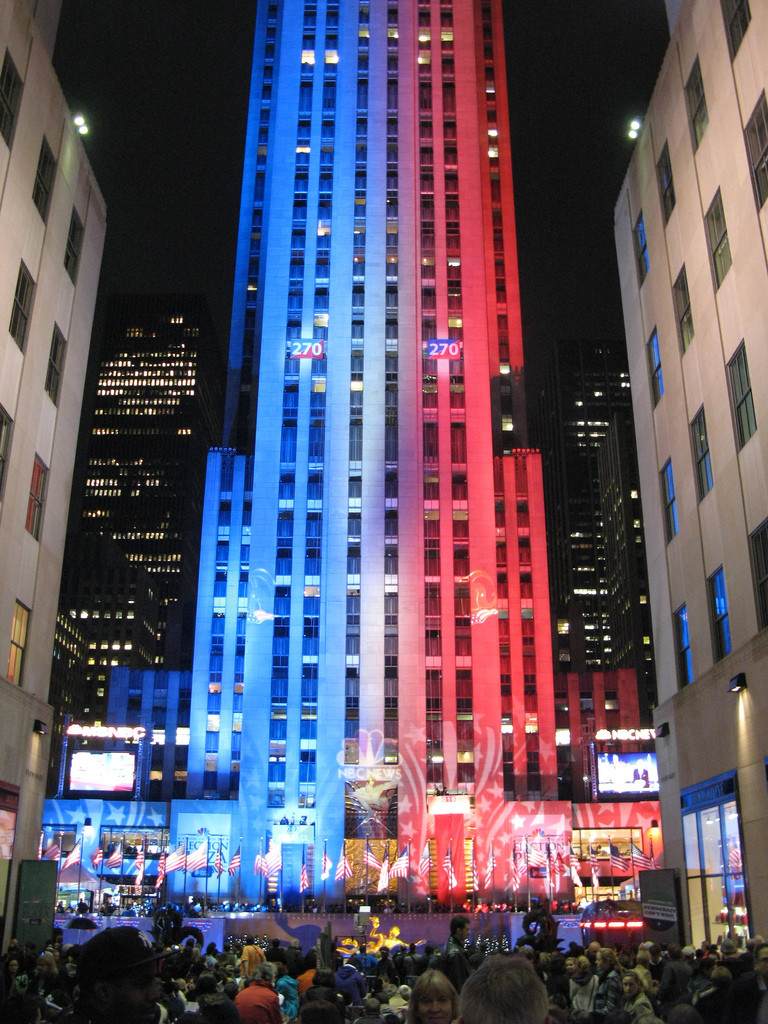 Photo of the Rockefeller Center in New York City during election night, 2008. Projected lights make half the building look blue, half red, representing the Democrats and Republicans. A row of American flags lines the street beneath.