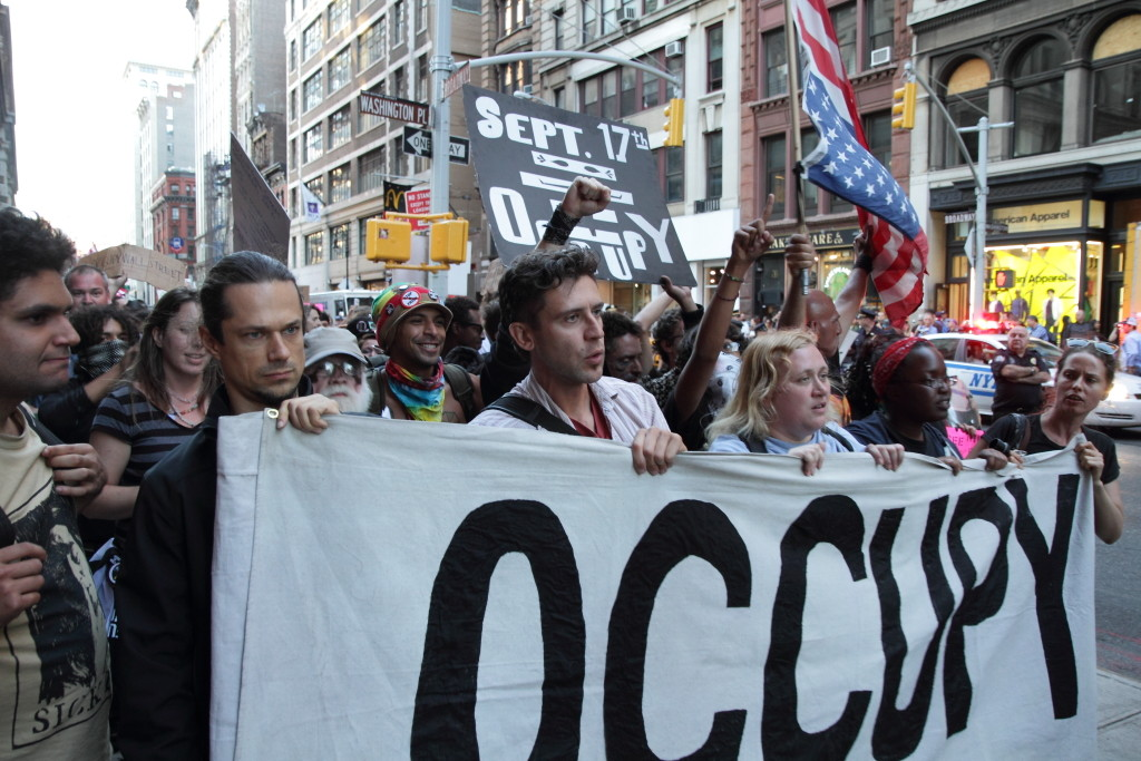 "Photo of the Occupy Wall Street protest showing a crowd of people marching on a street holding a banner that reads ""OCCUPY."""