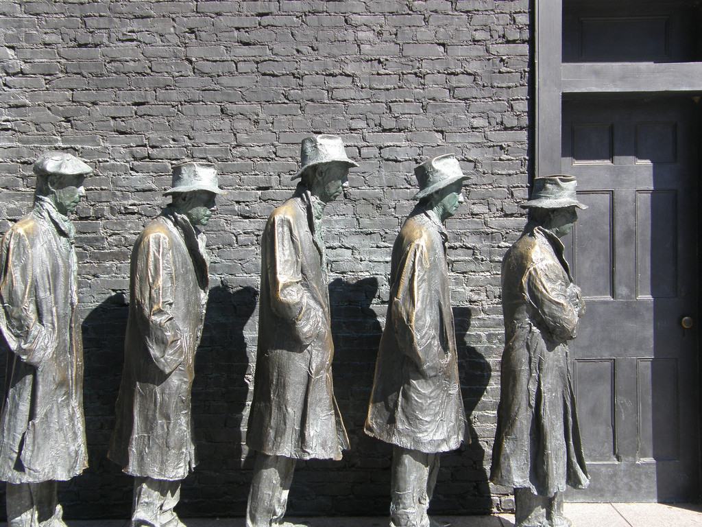 Photo of a scene at Franklin Delano Roosevelt Memorial, which includes four bronze figures—older men—waiting in a bread line. They wear hats and old clothes.