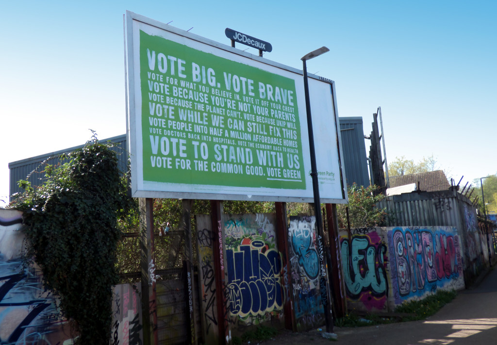 "Photo of a billboard advertising the Green Party. It reads,""Vote Big. Vote Brave. Vote for the common good. Vote green."" The sign stands above a wall that is filled with colorful graffiti."