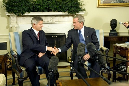 Photo of President George W. Bush in the Oval Office shaking hands with Prime Minister Marek Belka of Poland.