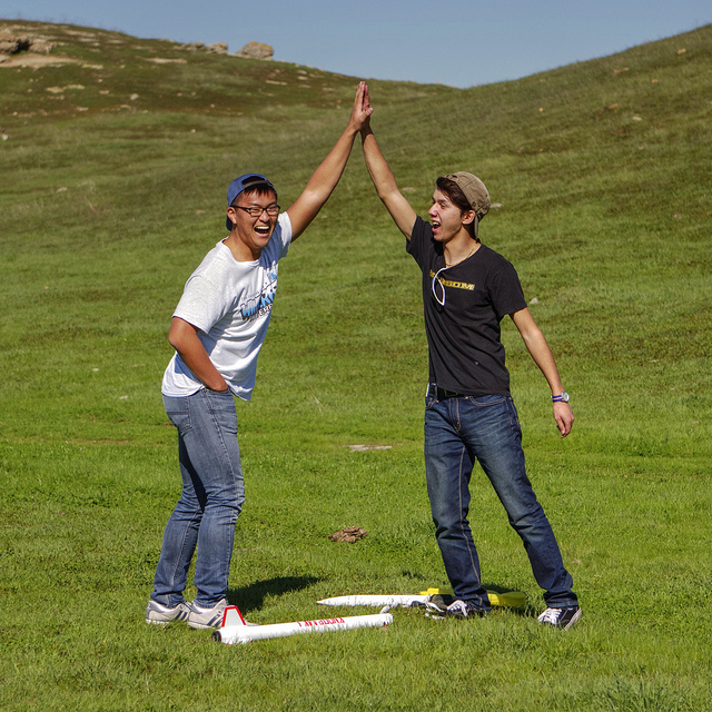 Two men high-fiving outside
