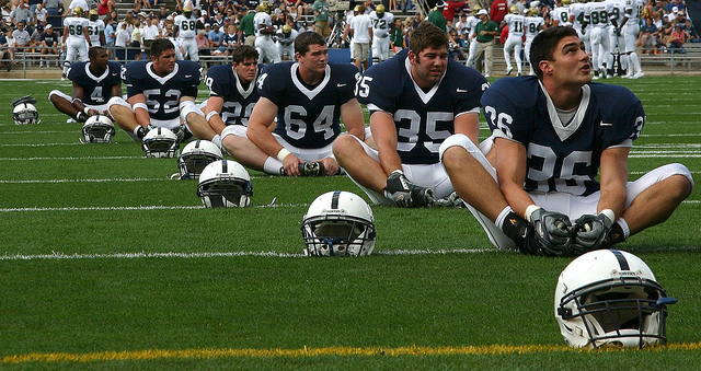 Football players stretching on field