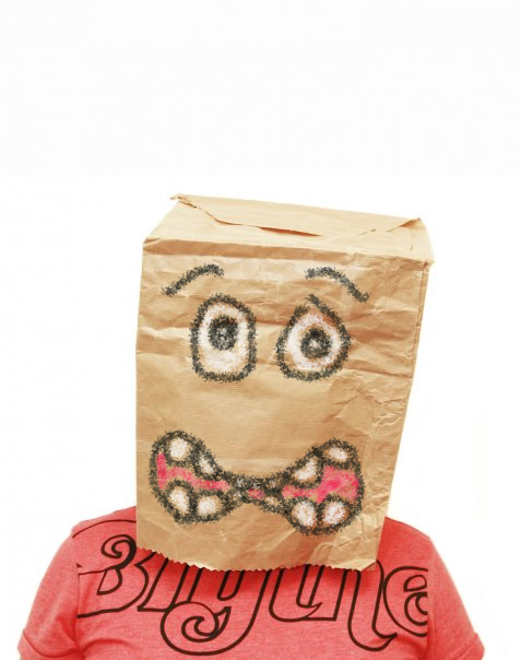 Person wearing paper bag on head with worried expression drawn on