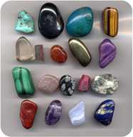 Several gems lined up for the photograph. These gems include jade and other precious rocks.