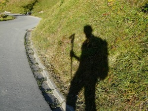 Photo showing a shadow of a man carrying a walking stick.  The shadow appears on a grassy hill alongside a road.