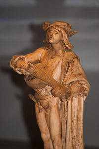 Photo of a statue in a museum.  Statue depicts man in medieval clothing playing a lyre and singing