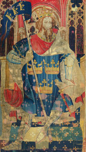 Worn tapestry depicting King Arthur seated on a throne, wearing a crown, cape, and tunic with three crowns on it.  He is holding a banner flag on a pole; the flag also has the same three gold crowns on a blue background