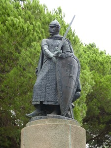 Photo of a statue outdoors, depicting a knight in chain mail, brandishing a sword and shield