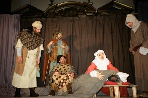 six actors on a stage. Central is a kneeling woman holding a man who appears passed out or dead. Around her kneel and stand four other men, dressed in medieval garb.
