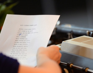 Photo looking over the shoulder of a person holding a piece of paper with a typed poem on it. It has been edited in one spot with handwriting
