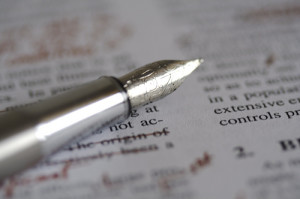 Photo of a fountain pen sitting on top of a printed page. Editing marks have been made in red on the page