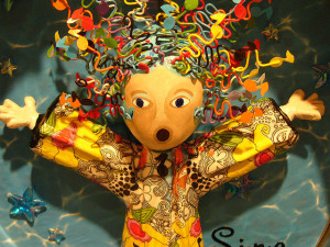 Photo of a wooden doll with mouth open and arms extended in a singing pose. The doll has brightly colored wire forms for hair and hand-drawn patterns on its shirt