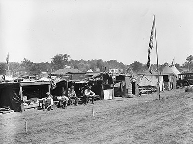 A photograph shows a row of tents with several veterans seated outside. An American flag is raised in the middle of the camp.