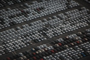 Photo of a large dealership parking lot with hundreds of cars parked in neat rows.