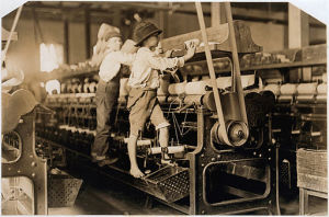 Black-and-white photo of two children standing and working on mill machinery