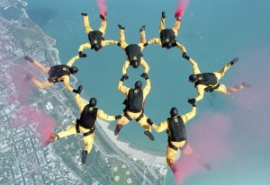 A group of eight people skydiving while holding hands to form a figure eight