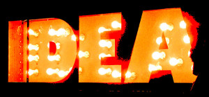 "Photo of a sign reading ""IDEA."" The letters are formed out of orange metal and lit up with exposed light bulbs, set against a black backdrop"